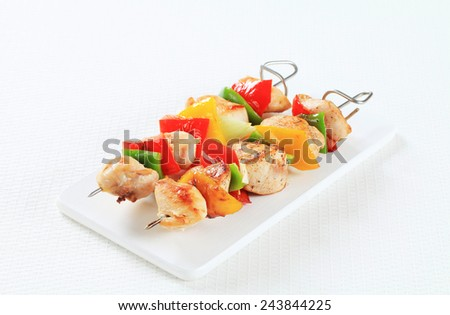 Chicken skewers on a cutting board - stock photo
