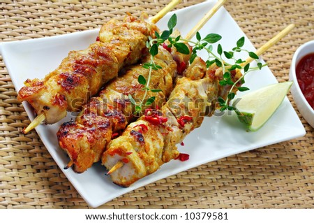Chicken skewers served with chili, lime, thyme, and a chili dipping sauce. - stock photo