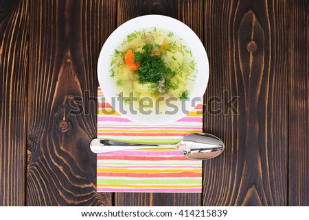 chicken soup and colorful napkin on wooden table. flat lay. top view - stock photo