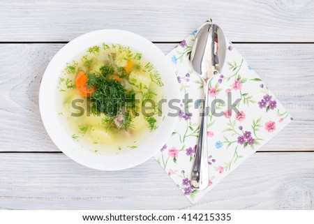 chicken soup and floral napkin. flat lay. top view - stock photo