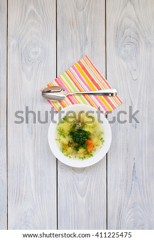 chicken soup and spoon on colorful napkin - stock photo