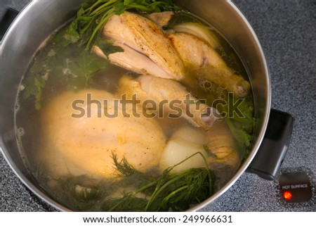 Chicken soup cooking in a pot on stove - stock photo