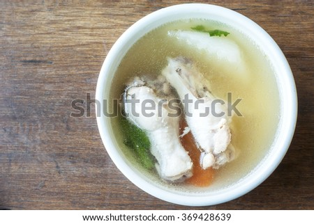 Chicken soup in a bowl placed on a wooden floor