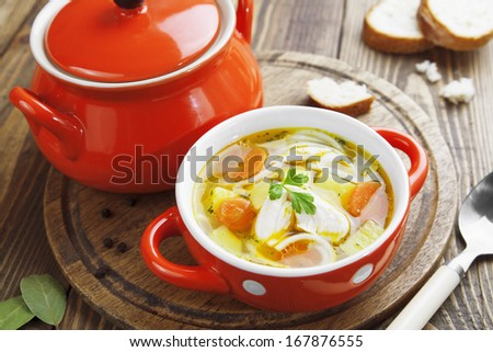 Chicken soup in an orange bowl on the table - stock photo