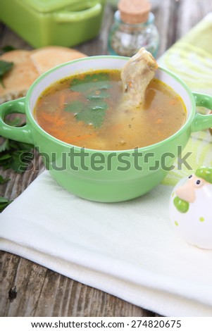 Chicken soup in green bowl on a wooden table