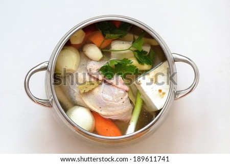 Chicken soup in the pot - soup with vegetables. Carrots, celery, parsley, onion, garlic - stock photo