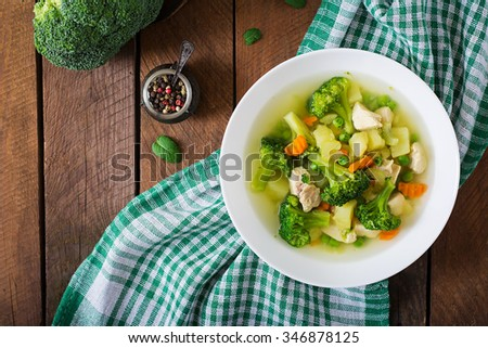 Chicken soup with broccoli, green peas, carrots and celery in a white bowl on a wooden background in rustic style. Top view  - stock photo
