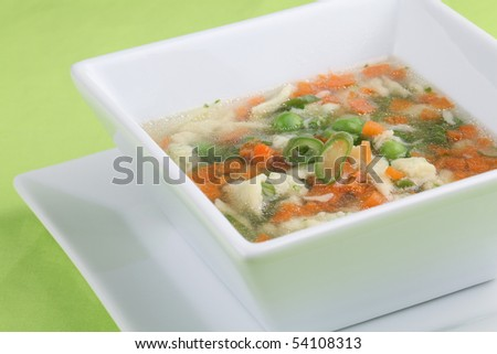 Chicken soup with carrot, green beans and peas - stock photo