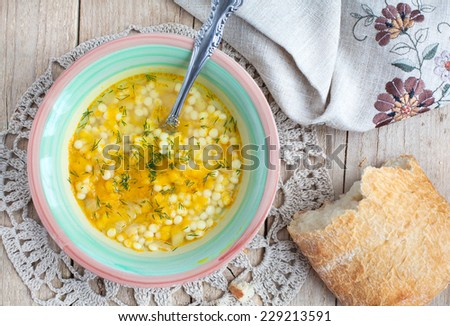 Chicken soup with carrots, Israeli couscous ptitim, dill and a piece of ciabatta, selective focus - stock photo