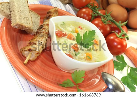 Chicken soup with eggs, noodles and greens on bright background