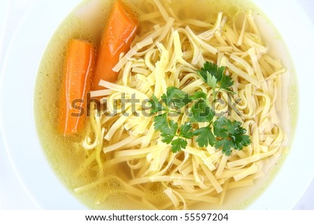 Chicken soup with macaroni and carrots decorated with parsley on a plate