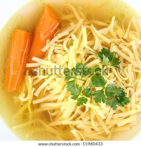 Chicken soup with macaroni and carrots decorated with parsley on a plate in close up - stock photo