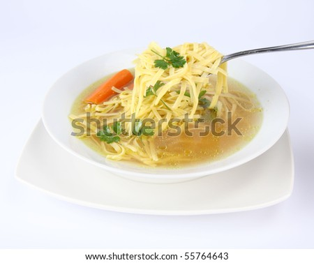 Chicken soup with macaroni and carrots decorated with parsley on a plate, some of it on a spoon - stock photo