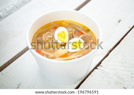 chicken soup with noodles and eggs - stock photo