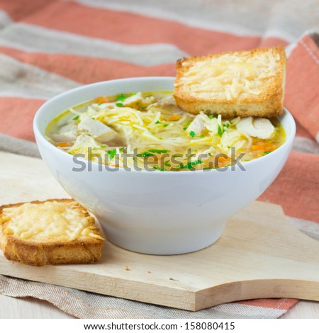 Chicken soup with noodles, carrots and cheese croutons - stock photo