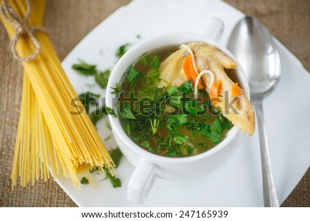 chicken soup with pasta and greens on a plate - stock photo