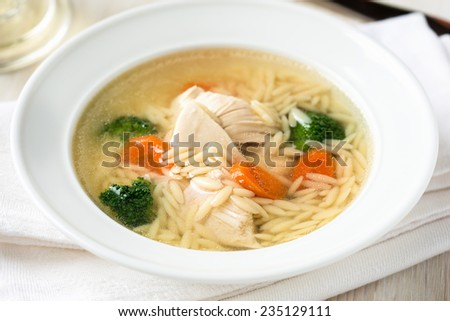 Chicken soup with vegetables and Italian pasta orzo - stock photo