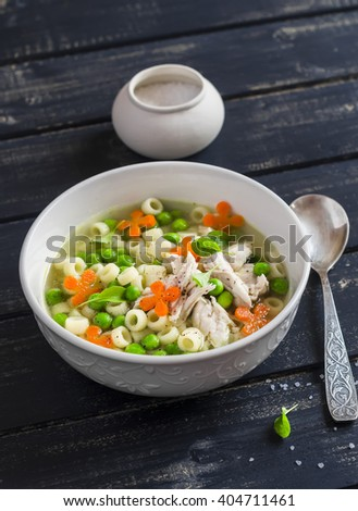 Chicken soup with vegetables and pasta on a dark wooden background - stock photo