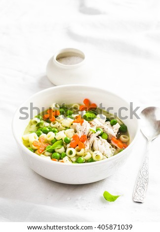 Chicken soup with vegetables and pasta on a light background - stock photo