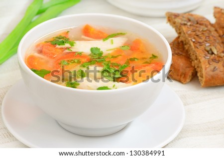 Chicken soup with vegetables in white bowl on a table