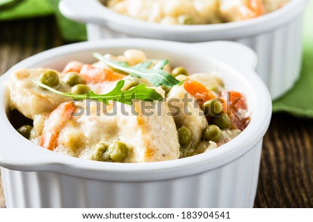 Chicken stew with carrot and green peas in a creamy white sauce