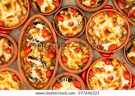 Chicken stews in stoneware cups served conceptually for mass together on the table, oval big stew surrounded with several small round stoneware crock cups - stock photo