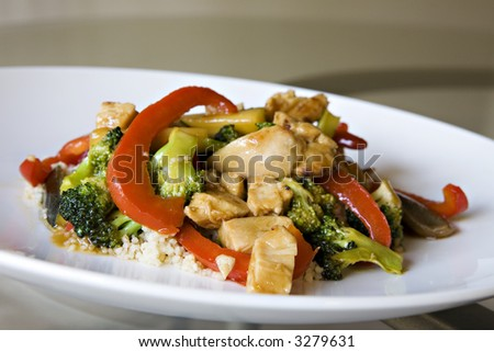 Chicken Stir Fry over Whole Wheat Couscous set on a Glass Table - stock photo