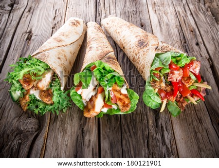 Chicken strips in Tortilla wrap on wood background. - stock photo