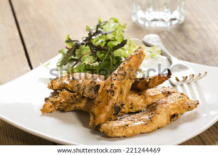 Chicken strips, on a white square plate with a side salad - stock photo