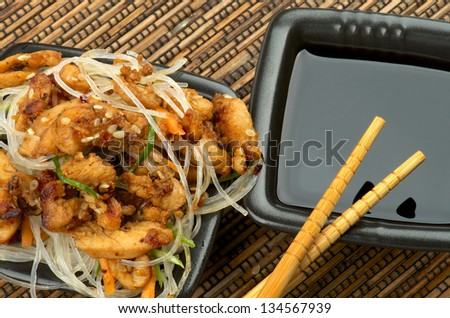 Chicken Teriyaki. Chinese Glass Noodles and Soy Sauce in Black Square Shape Bowls with Pair of Chopsticks on Straw mat background - stock photo