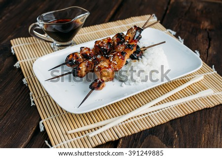 Chicken teriyaki skewers with brown rice on the table. Toning. Selective focus. - stock photo