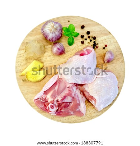 Chicken thigh cut into round board with garlic, basil, ginger isolated on white background - stock photo