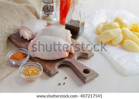 Chicken thighs. Spice. Chili pepper, soy sauce, pepper, mushrooms and peeled potatoes - stock photo
