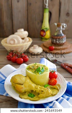 Chicken thighs with mushrooms in a creamy sauce with mashed potatoes on wooden table - stock photo