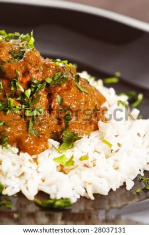 Chicken tikka masala served  with rice and garnished with cilantro leaves - stock photo