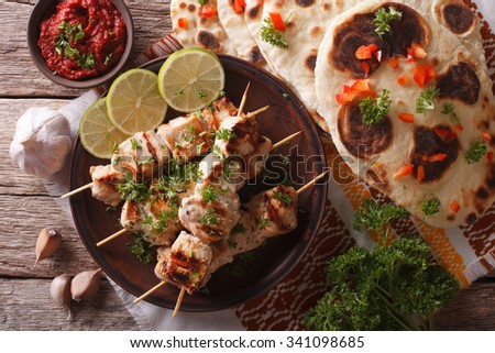 Chicken tikka on skewers, naan flat bread and chutney closeup. horizontal top view