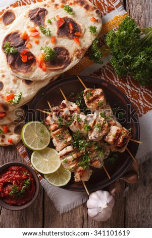 Chicken tikka on skewers, naan flat bread and chutney closeup. vertical top view