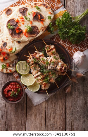 Chicken tikka on skewers, naan flat bread and chutney. vertical top view