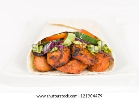 Chicken Tikka Wrap - BBQ Tandoori chicken tikka with salad wrapped in a flatbread on a white background. - stock photo