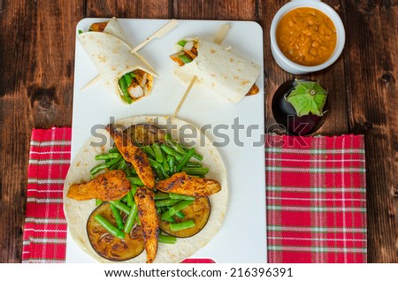 Chicken tortilla with beans and red curry on wood table - stock photo