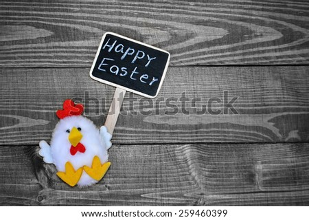 Chicken toy holding Happy Easter sign on wooden background - stock photo