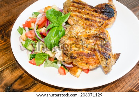 Chicken under a brick with panzanella salad. Pollo al mattone