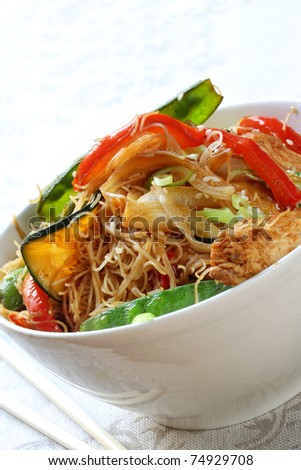 Chicken, vegetable and noodle stir-fry, in white bowl with chopsticks. - stock photo