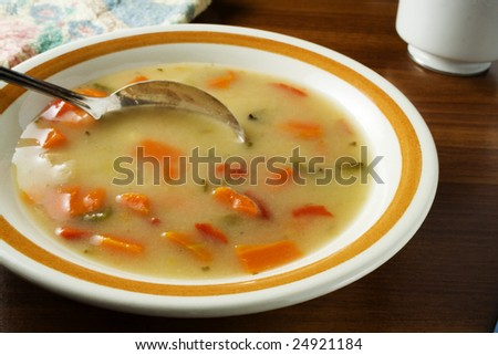 Chicken vegetable soup in bowl with spoon