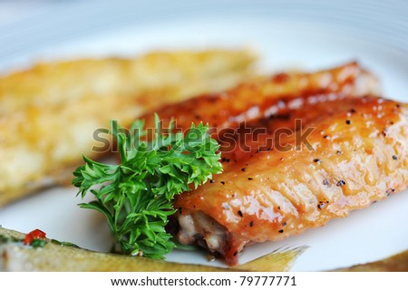 chicken wings and fish in plate. - stock photo