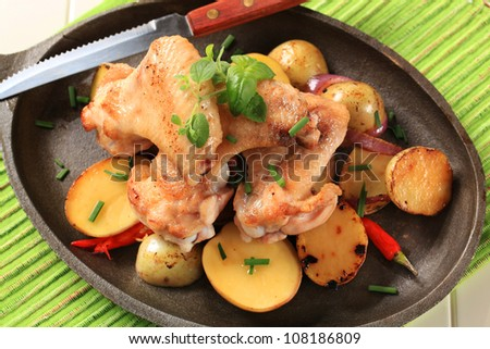 Chicken wings and potatoes sprinkled with chives - stock photo