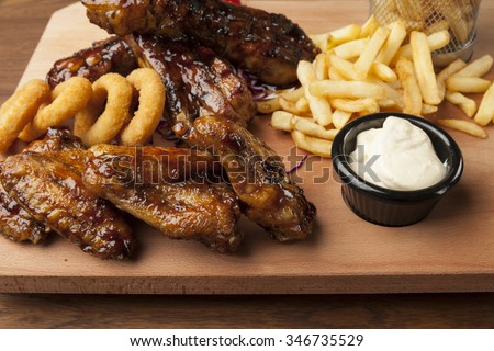 chicken wings and ribs with fries on wooden table