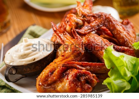 Chicken wings. Buffalo wings. Hot and spicy buffalo chicken wings. Barbecue buffalo chicken wings. Homemade buffalo wings with dip. Hot chicken wings. Buffalo wings in plate on wooden table. Spicy. - stock photo