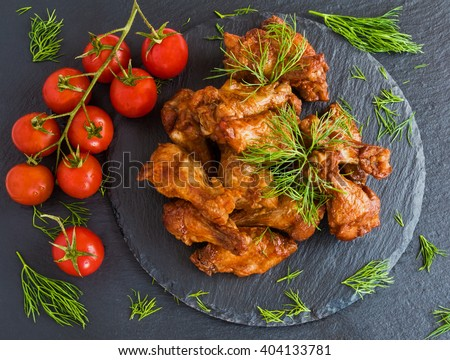 Chicken wings cooked with barbecue sauce on black stone background. Small cherry tomatoes and dill. Top view. - stock photo
