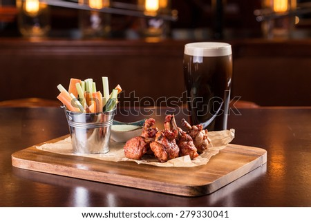 Chicken wings with blue cheese dip and glass of beer isolated on wooden table - stock photo